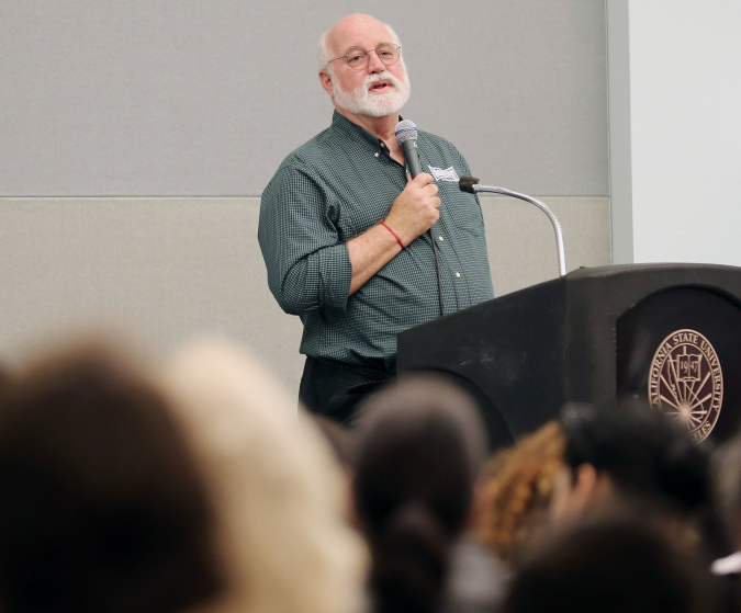 Rev. Greg Boyle speaks into microphone at a lectern in front of a crowd