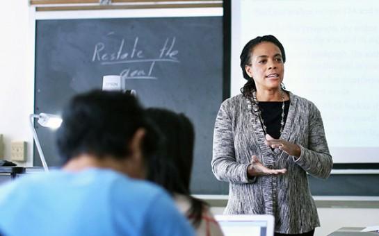Professor teaching room of students in front of blackboard