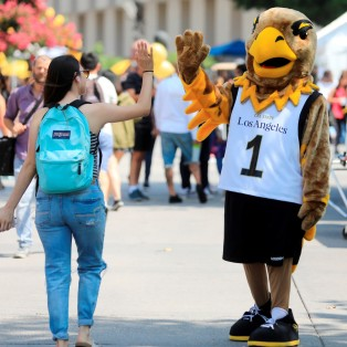 Eddie high fiving student on Main Walkway