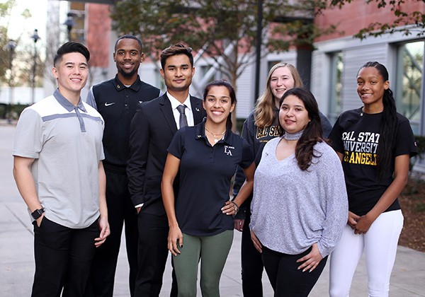 Seven students standing together smiling on campus